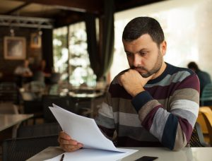 Foto: Ein junger und besorgt wirkender Mann liest einen Brief